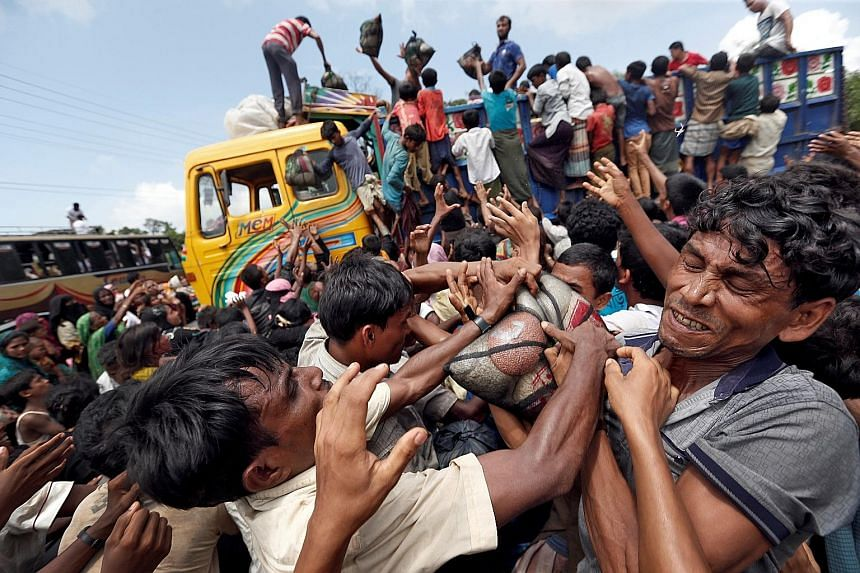 Above and left: Refugees scuffling for supplies and waiting for aid in Cox's Bazar, Bangladesh, on Saturday. While 430,000 Rohingya have fled into Bangladesh in the past month, tens of thousands of other displaced people remain in the northern part o