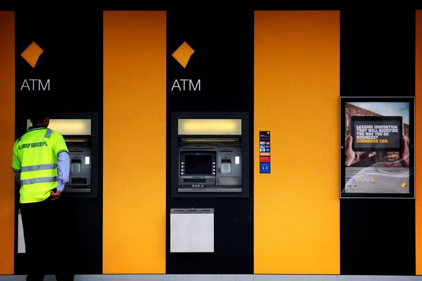A man uses a Commonwealth Bank ATM located outside a branch in Sydney.