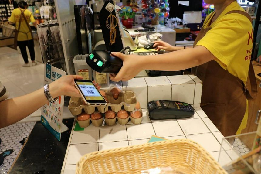A cashier scanning a bar code on a customer's phone as she opts to pay for her goods through the Alipay application.