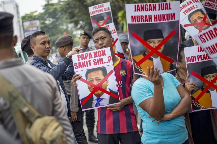 A group of demonstrators hold photographs of house speaker Setya Novanto during a rally in front of the South Jakarta court on Sept 12, 2017.
