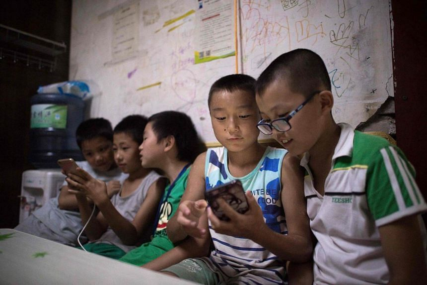 Children play smartphone games inside a room in a migrant village on the outskirts of Beijing, on Aug 17, 2017.