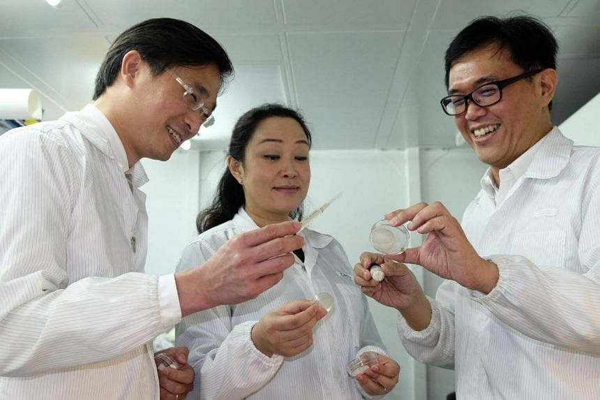 Assistant Professor Cleo Choong, Associate Professor Andrew Tan (right) and their clinical partner, Dr Marcus Wong, with various applications containing ANGPTL4.