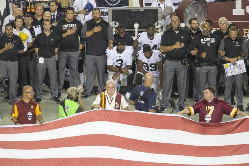 Players from the Oakland Raiders sit during the national anthem prior to their NFL game against the Washington Redskins, in Landover, Maryland, on Sept 24, 2017.