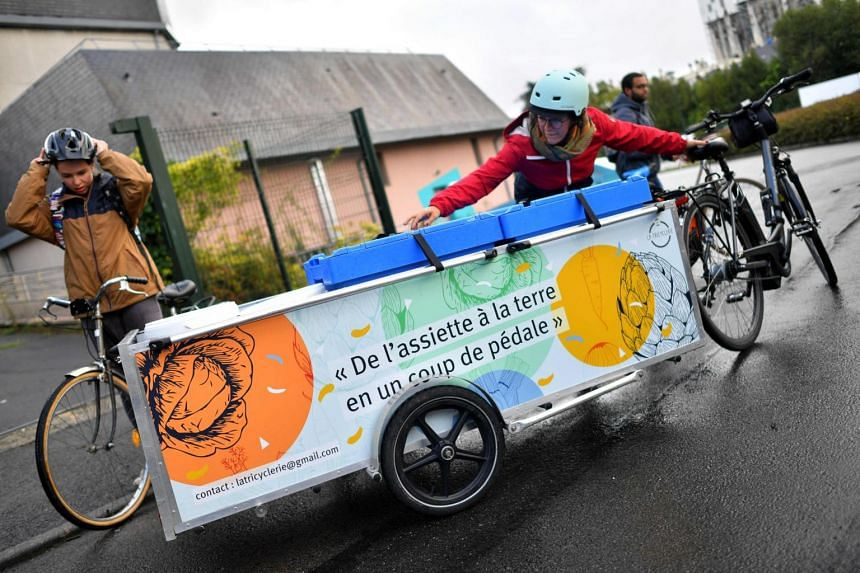 Members of La Tricyclerie association collect organic wastes from restaurants and companies to supply a compost in Nantes, western France, on Sept 11, 2017.