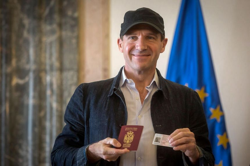 British actor Ralph Fiennes smiles after receiving a Serbian passport and ID card from Serbia's president in Belgrade on Sept 24, 2017.