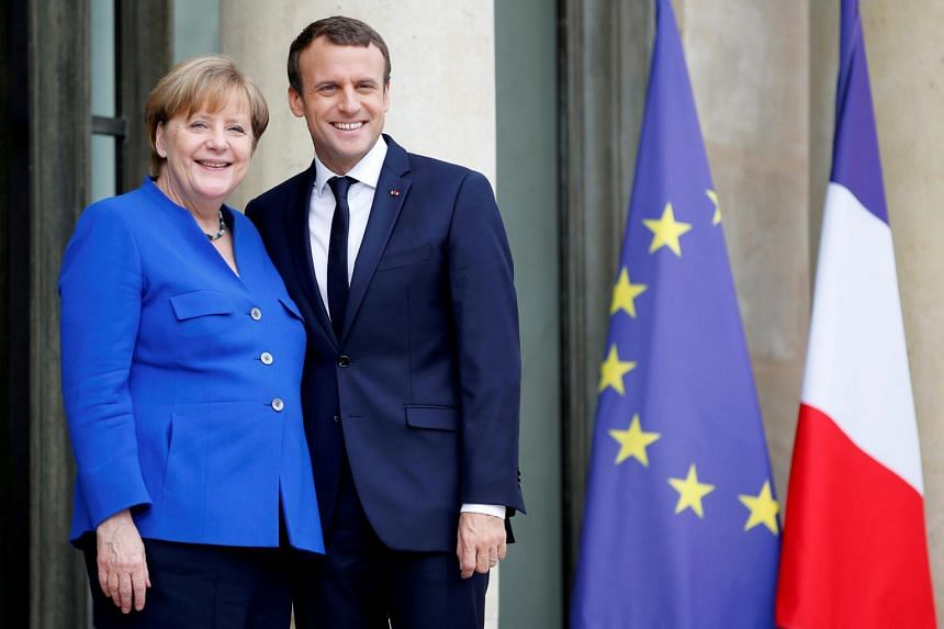 French President Emmanuel Macron arrives with German Chancellor Angela Merkel to attend a Franco-German joint cabinet meeting at the Elysee Palace in Paris, France, on July 13, 2017.