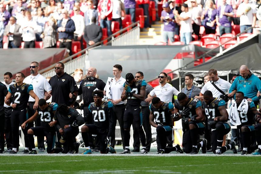 Jacksonville Jaguars players kneel during the US national anthem before the match at London's Wembley stadium on Sept 24, 2017.