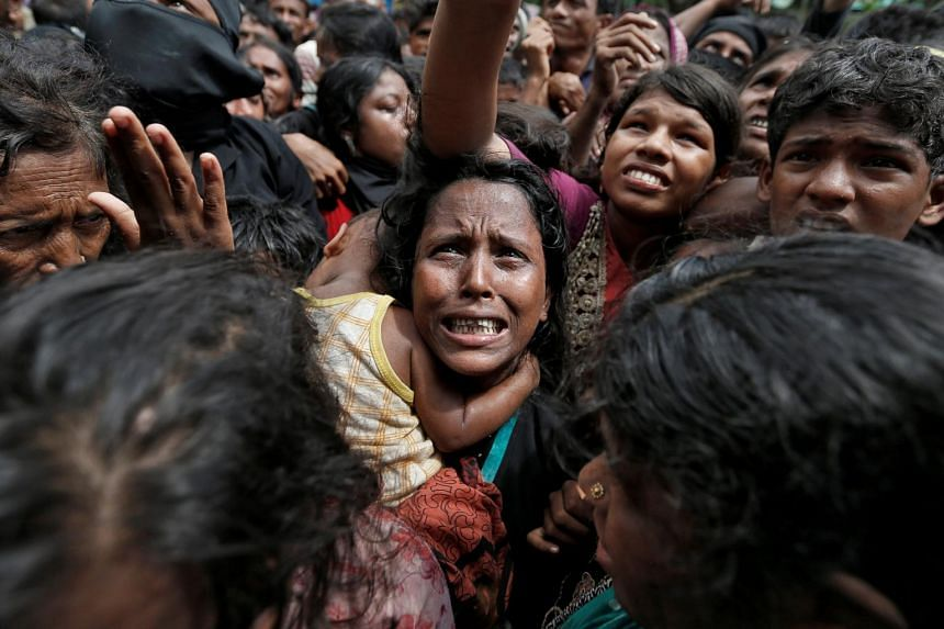A woman reacts as Rohingya refugees wait to receive aid in Cox's Bazar, Bangladesh, on Sept 21, 2017.