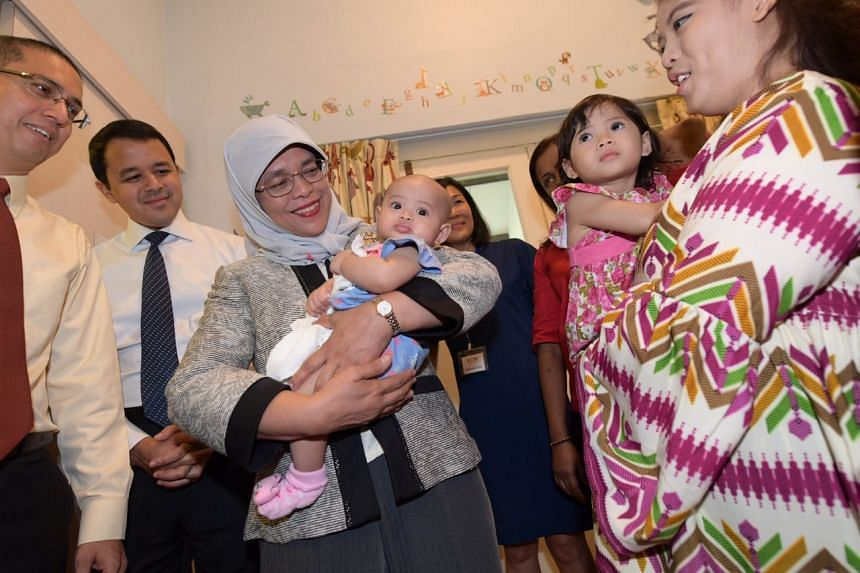 Madam President carrying Nurul Humaira, 4.5 months old, at Dayspring SPIN (Single Parents INformed INvolved and INcluded). Nurul's mother, Nayli Nur Damia (far right), 23, holding her two-year-old daughter, Zahra Inara, looks on.