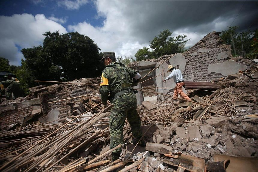 A soldier and a resident clear rubble from a destroyed house after an earthquake in San Juan Pilcaya, at the epicenter zone, Mexico, on Sept 25, 2017.