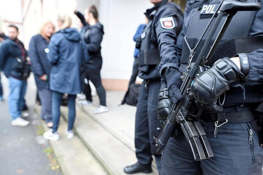 Police guard an entrance of the court before the start of a trial of five suspected Islamist militants, led by 33-year-old Iraqi known as Abu Walaa, accused of recruiting fighters for Islamic State in Syria, in Celle, Germany on Sept 26, 2017.
