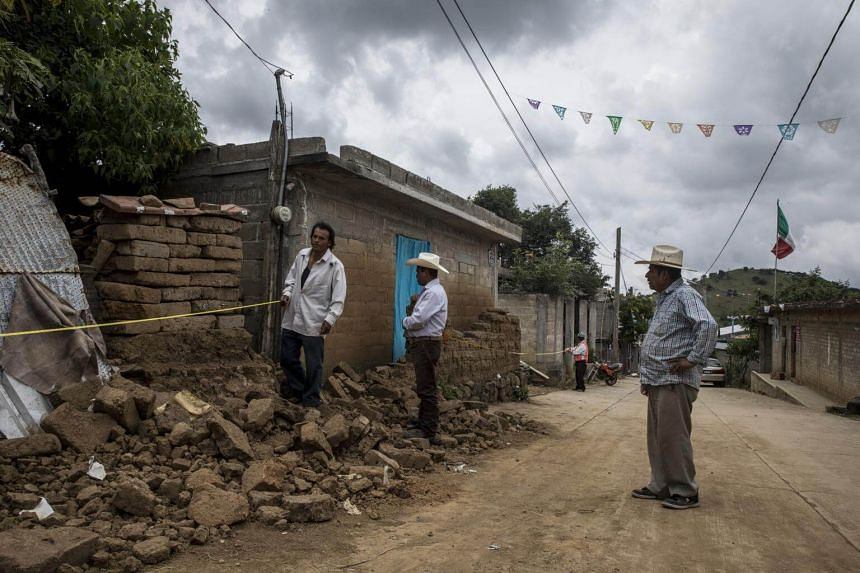 Men survey the damage from the earthquake on the main street in San Francisco Xochiteopan, Mexico, on Sept 23, 2017.
