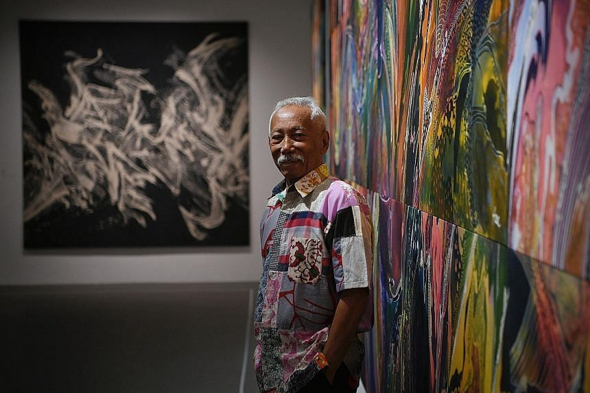 Batik artist Sarkasi Said with his artworks View Of Life (right) and Light (background) at his solo exhibition at the National University of Singapore Museum.