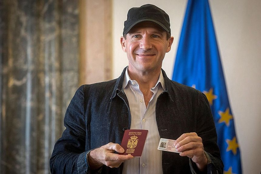 British actor Ralph Fiennes with his Serbian passport and identity card on Sunday.