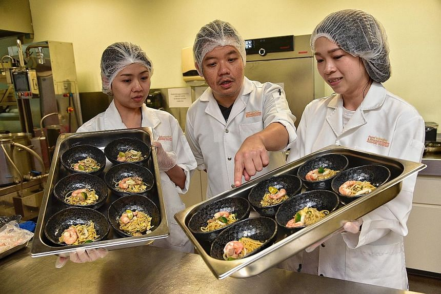 Members of the Food Innovation & Resource Centre team (from left) Wenie Chin, Martyn Wong Kang Loong and Ho Seeh Ming with the new noodle prototypes. The research centre has developed wholegrain yellow noodles made with beta-glucan, a soluble fibre,