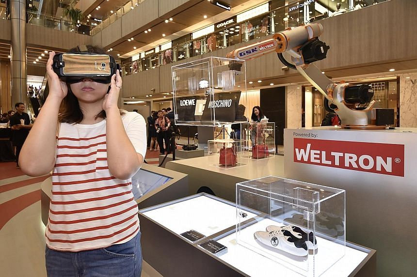 A large robotic arm, the centrepiece of the display at Paragon, picks up and moves different boxes with fashion pieces so that shoppers can get an all-round view of the items (above).
