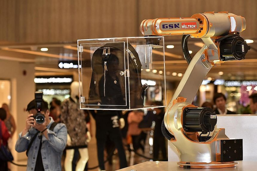 A large robotic arm (above), the centrepiece of the display at Paragon, picks up and moves different boxes with fashion pieces so that shoppers can get an all-round view of the items.