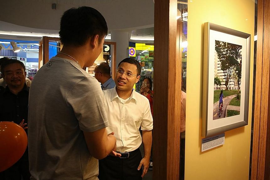 Foster child Timothy (not his real name), 17, showing Mr Desmond Lee, the Minister for Social and Family Development, his photograph at the exhibition. It is one of many that foster charges took to show the positive impact on their lives.