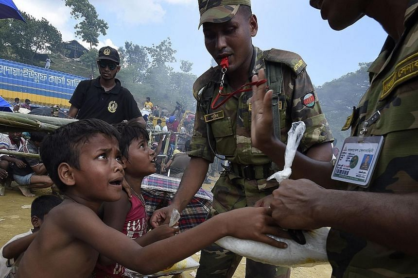 Above: Bangladeshi soldiers distributing rice to Rohingya refugees at a camp near Gumdhum yesterday. Left: A supporter of Myanmar leader Aung San Suu Kyi at a rally in Yangonon Sunday. Ms Suu Kyi has said the Myanmar government is taking measures to