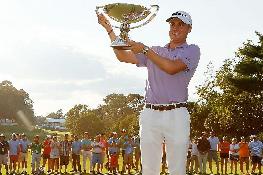 Justin Thomas hoisting the coveted FedExCup on the 18th green, after finishing a stroke behind fellow American Xander Schauffele in the Tour Championship at East Lake Golf Club on Sunday in Atlanta, Georgia.
