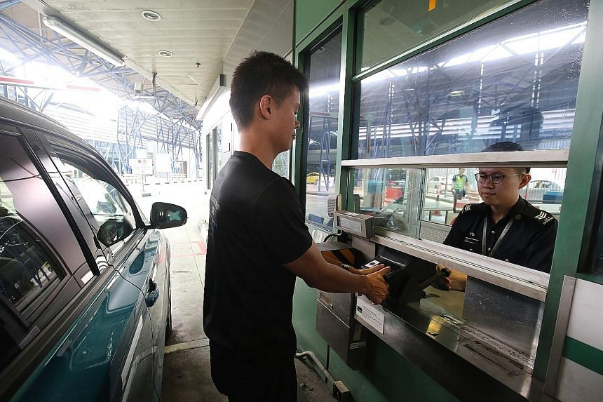 A traveller having his thumbprints scanned at the Woodlands checkpoint. ICA officers will be present to help people use the BioScreen machines.