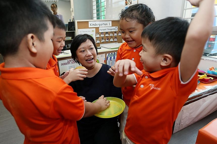 """Ms Karina Anne Lee, 38, with some children from My First Skool in Toa Payoh yesterday. The assistant teacher says she was inspired by the """"energy and passion"""" of the pre-school teachers who nurtured her three children."""