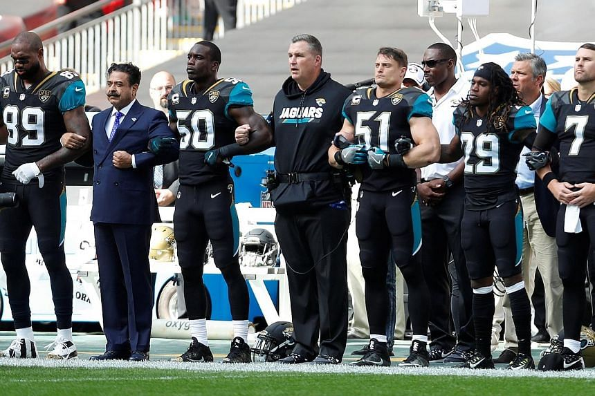 From far left: Jacksonville Jaguars owner Shahid Khan and head coach Doug Marrone linking arms with players during the national anthem before they played the Baltimore Ravens at Wembley Stadium in London on Sunday, while members of the Houston Texans