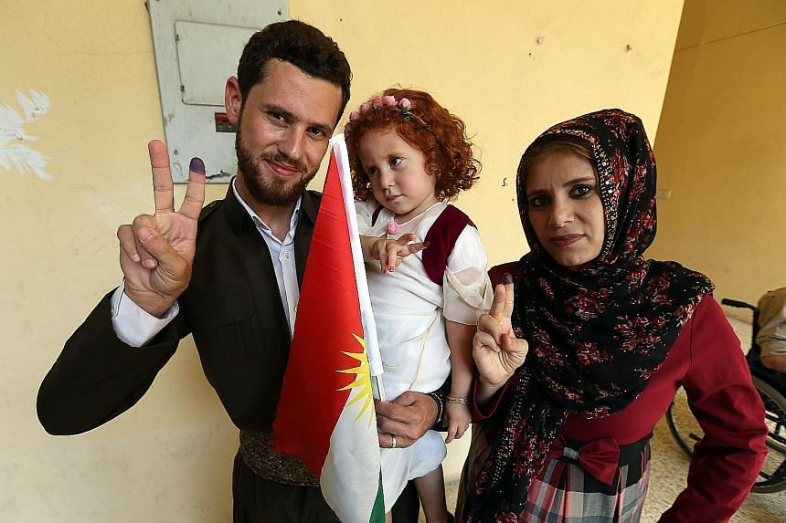 Iraqi Kurds showing their inked fingers after voting in the independence referendum in Erbil, northern Iraq's Kurdistan region, yesterday.