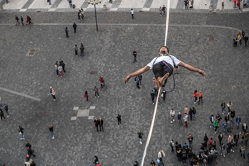 A participant balancing precariously on a slackline over the Old Town Square in Prague, the capital of the Czech Republic, yesterday. The daredevil feat was part of a campaign in support of people living with diabetes.