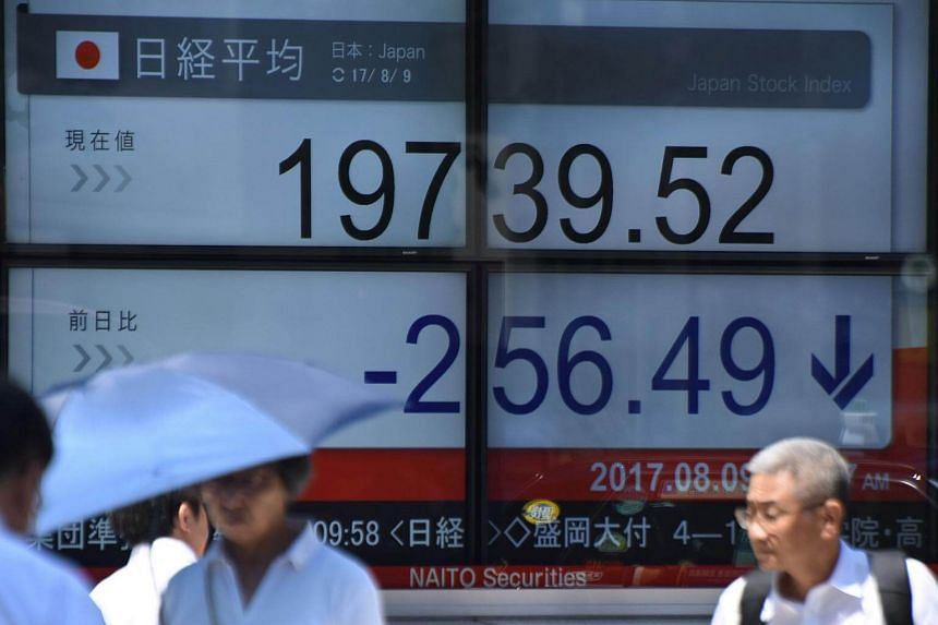 Pedestrians walk past a stock quotation board flashing the Nikkei 225 key index of the Tokyo Stock Exchange in front of a securities company in Tokyo, on Aug 9, 2017.
