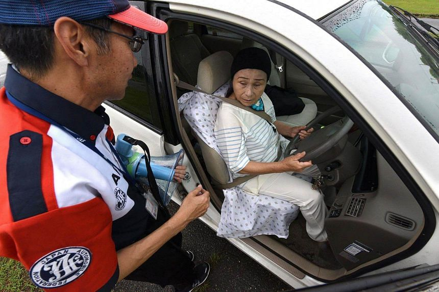 An instructor (left) interacting with an elderly student at a driving school for senior citizens, managed by the Japan Automobile Federation (JAF), in Kanuma, Tochigi prefecture on July 23, 2017.