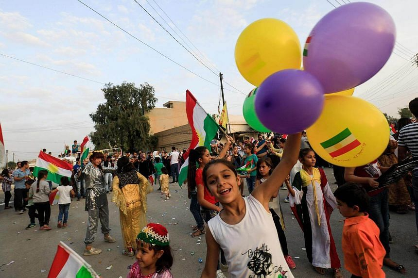 A Syrian Kurdish girl celebrates with balloons in the northeastern Syrian city of Qamishli on Sept 25, 2017.