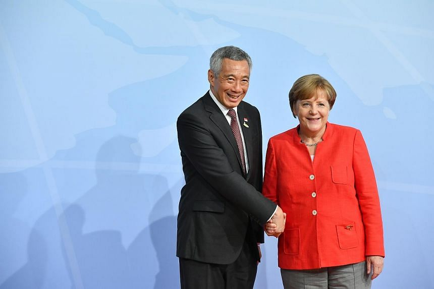 Prime Minister Lee Hsien Loong meeting German Chancellor Angela Merkel during the official welcome of the G20 Participants in Hamburg Messe, on July 7, 2017.