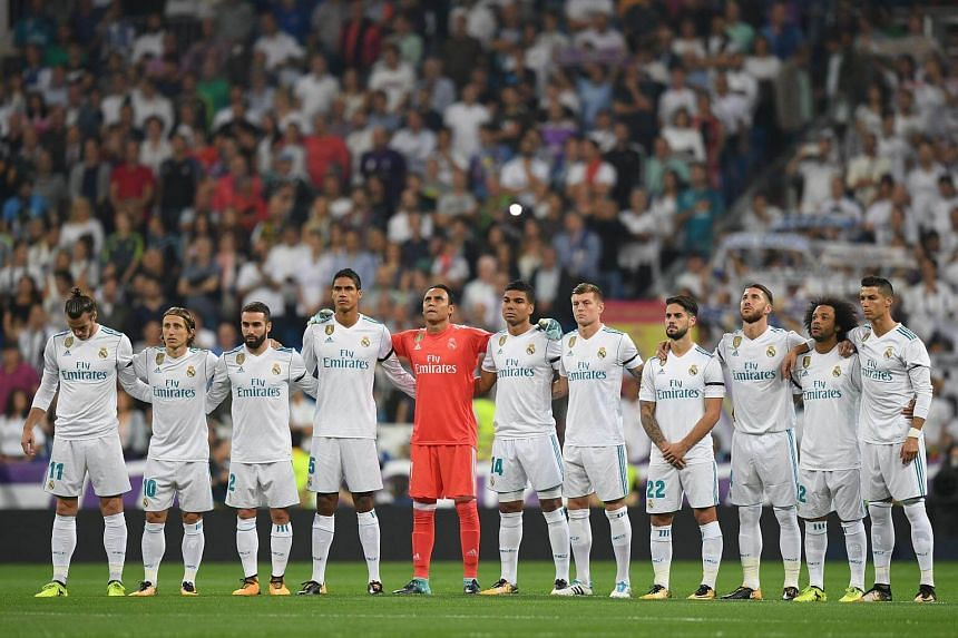 Real Madrid players line up before a football match at the Santiago Bernabeu stadium in Madrid on Sept 20, 2017.