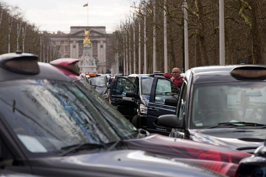 A driver standing by his vehicle as taxi drivers block The Mall as they demonstrate in central London against Uber.