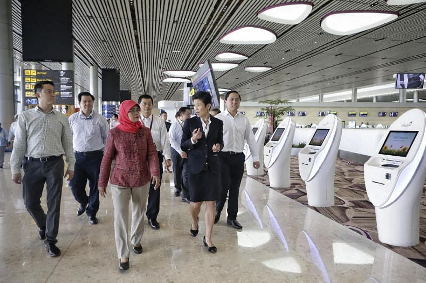 President Halimah Yacob walking past self check-in counters during her visit to Changi Airport Terminal 4 on Sept 26, 2017.