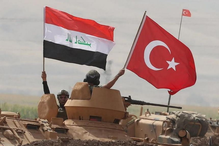 Soldiers hold a Turkish (centre) and Iraqi (left) national flag while standing in the turret of a Turkish armored vehicle participating in a military exercise near the Turkish-Iraqi border in the Silopi district, in Sirnak City on Sept 26 2017.