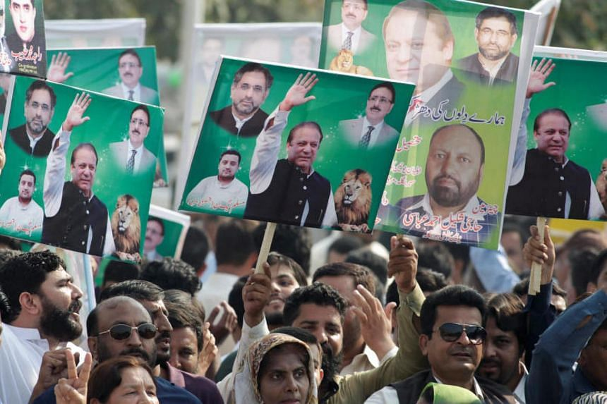 Supporters of Pakistan's former Prime Minister Nawaz Sharif hold his pictures during his appearance before the accountability court in connection with the corruption references filed against him, in Islamabad, Pakistan on Sept 26, 2017.