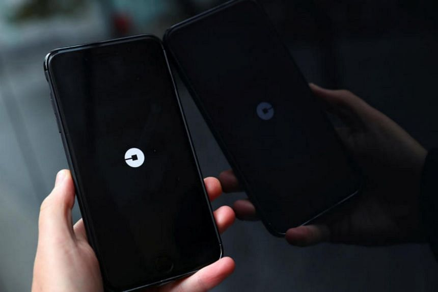 The Uber logo is seen on mobile telephone in London on Sept 25, 2017.