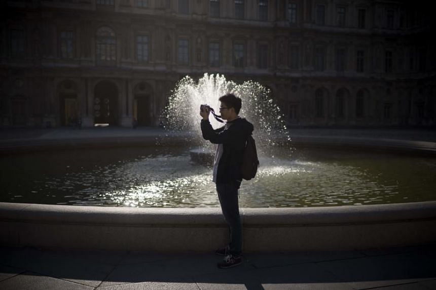 A tourist takes pictures near the fountain on the Place carree or Court Square at the Louvre Museum in Paris.