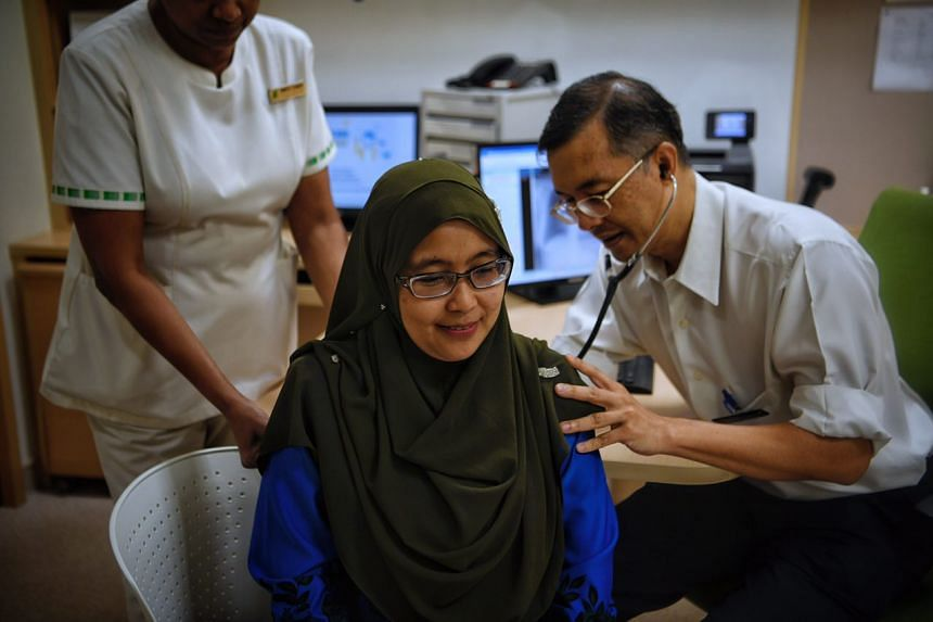 Professor Julian Thumboo, a senior consultant at Singapore General Hospital's Department of Rheumatology and Immunology, examining lupus patient Kartina Mohamad on Tuesday (Sept 26).