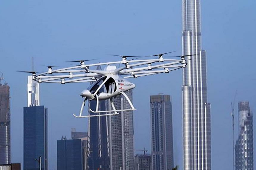 """A two-seater """"hover taxi""""  is seen flying in a """"concept"""" flight in Dubai in an mage provided by United Arab Emirates News Agency (WAM) on Sept 25, 2017."""