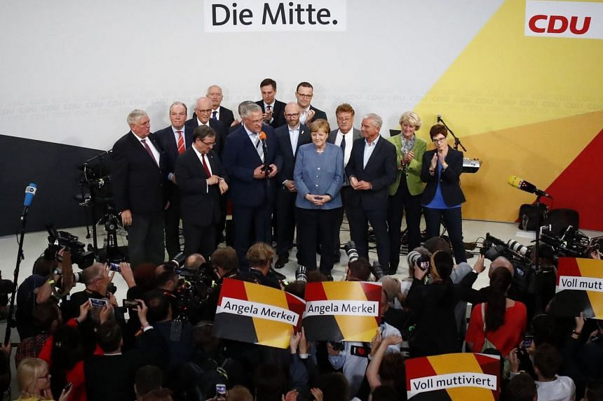Dr Angela Merkel being congratulated by members of her party in Berlin on Sunday. Damaged by her decision in 2015 to allow one million refugees into Germany, her conservative Christian Democratic Union secured 33 per cent of the vote in the general e