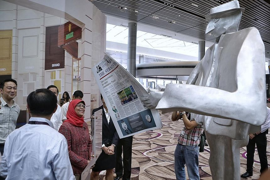 President Halimah Yacob viewing sculptures in the departure transit area during her visit to Changi Airport's Terminal 4 yesterday. She also viewed some of the technology being used to boost efficiency and security.