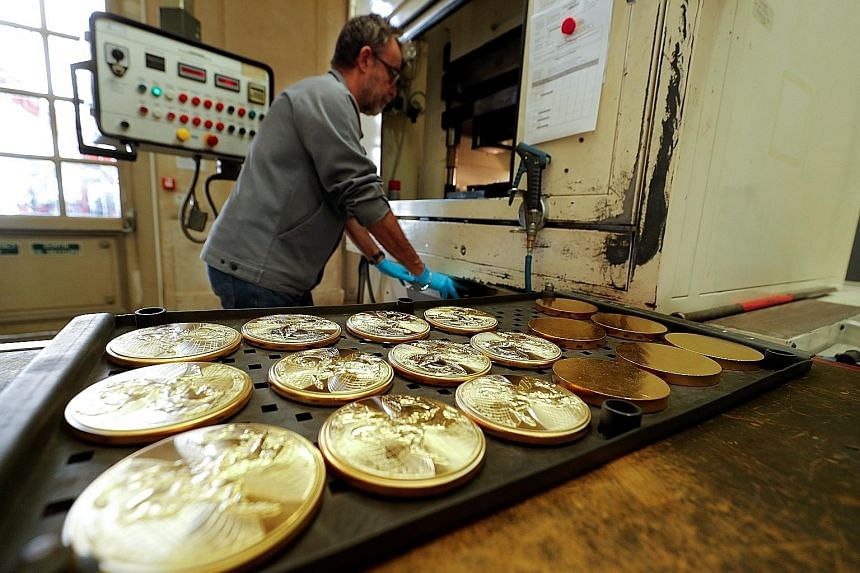 An employee mans a stamping machine at the factory of the Monnaie de Paris (Paris Mint) last Thursday, ahead of its reopening in Paris, France. After more than 1,000 years of service, the mint opened to the public a vast exhibition of treasures, coll
