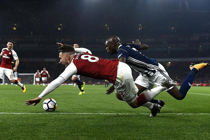 Arsenal's Aaron Ramsey is fouled by West Brom's Allan Nyom for a penalty, from which the Gunners score to wrap up a 2-0 win in the English Premier League match at the Emirates Stadium in London.