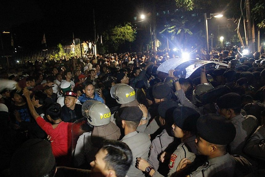 Anti-communist protesters clashing with police outside the Indonesian Legal Aid Foundation building in Jakarta on Sept 18. The mob had gathered at the location earlier on Sept 17 to protest against a suspected gathering of the long-defunct Communist