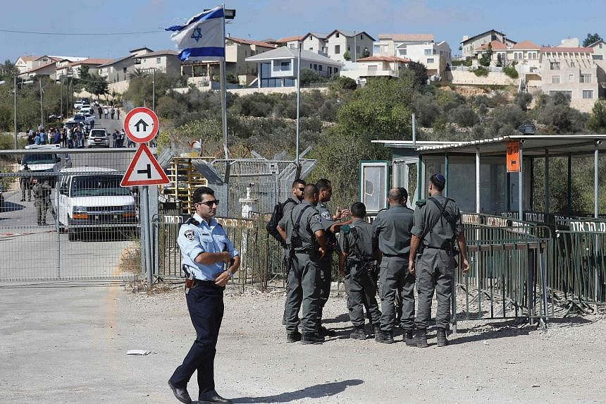 Israeli security forces outside a damaged security post at the entrance to the West Bank settlement of Har Adar, where the Palestinian man, who had domestic troubles, opened fire on security personnel yesterday.