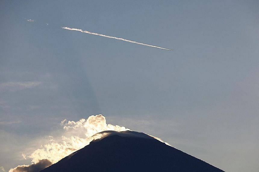 (Above) An airliner flying past Mount Agung, a volcano on the highest alert level, on the resort island of Bali yesterday. Singapore-based airlines Singapore Airlines, Scoot, AirAsia and Jetstar said their flights were operating normally yesterday, a