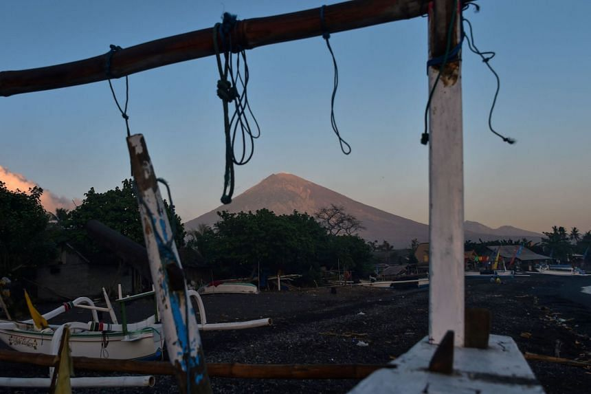 Mount Agung looms in the background at dawn past fishing boats parked ashore at Amed beach, in Bali, on Sept 27, 2017.